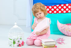 Little cute curly girl in pink pajamas watching the book sitting on the floor in children's bedroom. stock photography