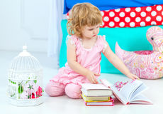 Little cute curly girl in pink pajamas watching the book sitting on the floor in children's bedroom. royalty free stock photos