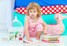 Little cute curly girl in pink pajamas watching the book sitting on the floor in the children's bedroom. stock photos