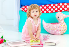 Little cute curly girl in pink pajamas watching the book sitting on the floor in the children's bedroom. royalty free stock image