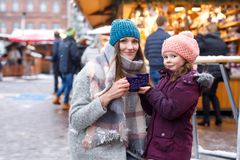 Little cute daughter and mother with cup of steaming hot chocolate or children punch. Happy child girl and beautiful. Women on Christmas market in Germany royalty free stock images
