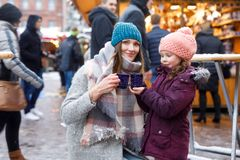 Little cute daughter and mother with cup of steaming hot chocolate or children punch. Happy child girl and beautiful women on Christmas market in Germany royalty free stock photography