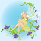 Little cute forest fairy sitting on beautiful wild. Flowers blond Royalty Free Stock Photos