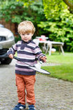 Little cute funny kid boy playing badminton in domestic garden Stock Images