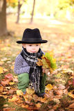 Little cute gentleman in a black hat in autumn park Stock Image