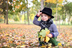 Little cute gentleman in a black hat in autumn park Royalty Free Stock Photos