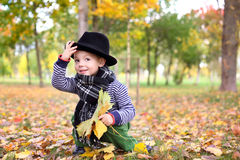 Little cute gentleman in a black hat in autumn park Stock Photography
