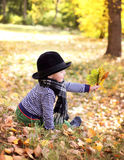 Little cute gentleman in a black hat in autumn park Stock Photos