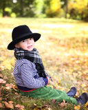 Little cute gentleman in a black hat in autumn park Stock Photo