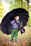 Little cute gentleman in a black hat in autumn park Royalty Free Stock Photo