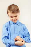 Little cute gentleman fastened the buttons on sleeve bright shirt Royalty Free Stock Photo