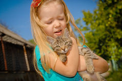Little cute girl affectionately hugging kitten. Kids play outdoors and hugging kitten Stock Photo