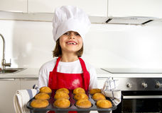 Little and cute girl alone in cook hat and apron presenting and showing tray with muffins smiling happy Royalty Free Stock Photo