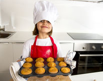 Little and cute girl alone in cook hat and apron presenting and showing tray with muffins smiling happy Royalty Free Stock Images