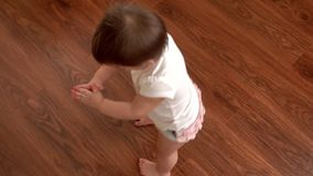 Little cute girl baby spins on its axis, loses balance and falls in slow motion stock footage