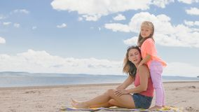 Little cute girl and young mother at beach. Little cute girl baby and young mother at beach. Mom sits on the shore, and her daughter is coming from behind. The Royalty Free Stock Images