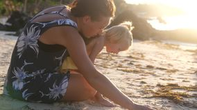 Little cute girl baby and young mother sitting on the beach, chatting during amazing sunset. slow motion. 3840x2160. 4k stock footage
