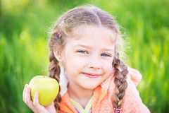 Little cute girl on a background of green grass with an apple Royalty Free Stock Photos