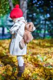 Little cute girl with a backpack-bear walks in the Stock Photos