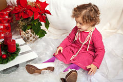 Little cute girl with beads and in mother's shoes Royalty Free Stock Images
