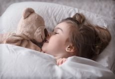Little cute girl in bed with toy stock image