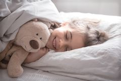 Little cute girl in bed with toy royalty free stock photos
