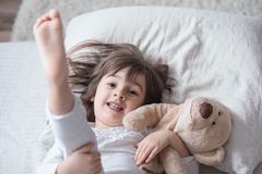 Little cute girl in bed with toy royalty free stock photography