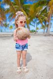 Little cute girl with a big coconut in palm grove Stock Images