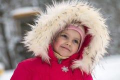 Little cute girl in a big fur hood thinks about something good. A little cute girl in a big fur hood thinks about something good Royalty Free Stock Photo