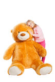 Little cute girl with big smile holding huge Teddy Stock Images