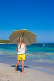 Little cute girl with big yellow umbrella walking Stock Images