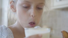 Little cute girl biting off a piece of patty and drinks it down with milk, then looks into the camera, smiling and shows stock footage