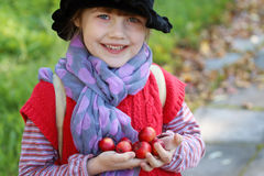 Little cute girl in black hat holds red apples Stock Photos