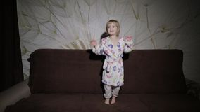 Little cute girl with blond hair jumps on sofa. Bathrobe clothes. Happy. Little cute girl with blond hair jumps on sofa. Bathrobe clothes. Feels happy. Slow stock footage