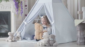Little cute girl with blond hair sitting surrounded by soft toys stock video
