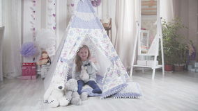 Little cute girl with blond hair with soft toys in DIY tent stock video