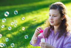 Little cute girl blowing soap bubbles outdoors Royalty Free Stock Photography