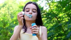 Little cute girl blowing soap bubbles stock video footage