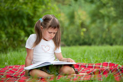Little cute girl with book on plaid in park Stock Photo