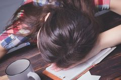 Little cute girl is bored and tired with doing her homework stock photo