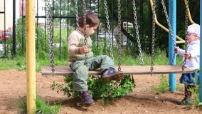 Little cute girl and boy are playing on swings. At playground stock video footage