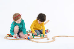 Little cute girl and boy roll trains on wooden railway Stock Images