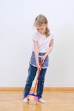 Little cute girl brooming floor. Stock Photo