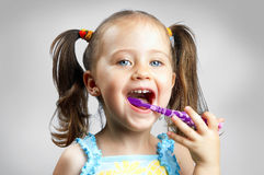A little cute girl brushing her teeth Stock Image