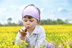 Little cute girl with a butterfly. Little cute girl in a field of beautiful yellow flowers holding a butterfly on the palms and blowing on it Stock Images