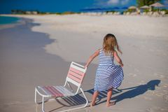 Little cute girl with chair at beach during Royalty Free Stock Photos
