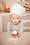 Little cute girl with chef hat holding cake Royalty Free Stock Photography