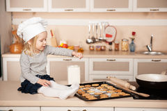 Little cute girl with chef hat preparing cookies Stock Photo