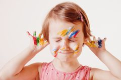 Funny portrait of cute cheerful child girl colourful painted hands and fac. Little cute girl with children`s colourful makeup showing painted hands. Happiness stock photography