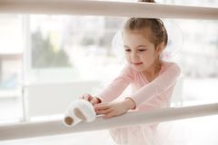 Little cute girl in class in ballet studio. Little ballerina girl in a pink tutu. Adorable child dancing classical ballet in a white studio. Children dance. Kids royalty free stock image